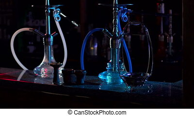Two hookahs stand on the bar counter in a hookah bar in the dark.