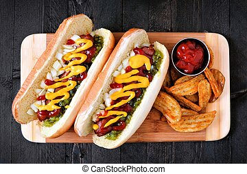 Two hot dogs fully loaded with toppings and potato wedges on...