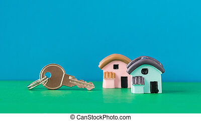 Two house with a key on a green Desk on blue background.