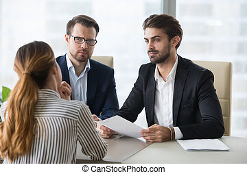 Two hr managers looking with disbelief at female applicant.