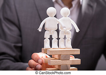 Two Human Figures Standing On Top Of Stacked Wooden Blocks