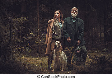 Two hunters with dogs and shotguns in a traditional shooting...