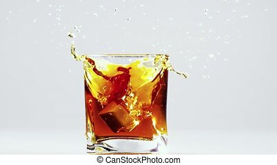 Two ice cubes falling into glass with brandy. Slow motion