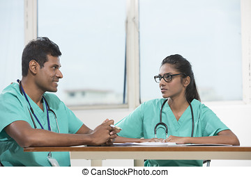 Two Indian doctors sitting working at a desk together