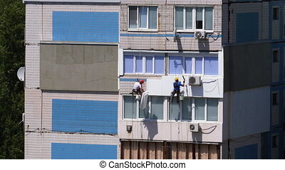 Two Industrial Climber Suspended on Ropes Performs Work on Insulation Facade of High-rise Building using styrofoam. Industrial alpinism. Warms an old panel multi-story residential building using foam.