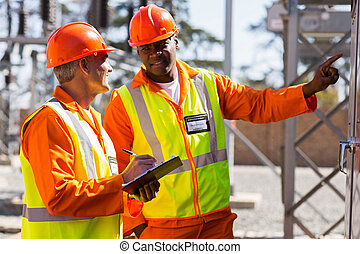 industrial electricians taking machine readings