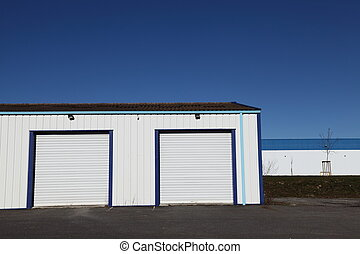 Two closed white corrugated industrial garage doors in a small warehouse and open tarmac in the foreground against blue sky