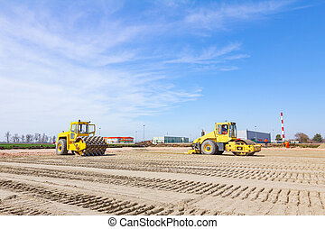 Two industrial rollers are compacting sand at construction ...