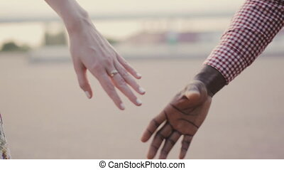 two interracial lovers joining hands - interracial couple...