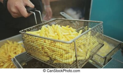 Two iron containers with fried potatoes in deep frying in...