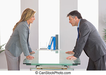 Two irritated businesspeople arguing on each side of a desk...