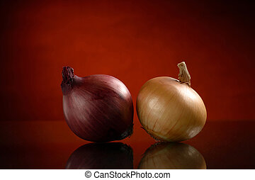 Two isolated onion bulbs on a dark orange background