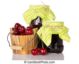 Two jars of jam a wooden bucket with sweet cherries