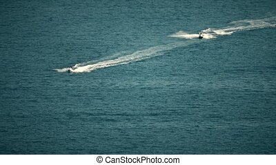 Two jet ski riders at sea. Telephoto lens shot - Jet ski...