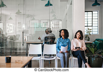 Two job applicants waiting in an office to be interviewed