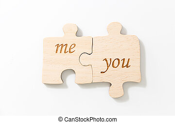 Two joined pieces of wooden puzzle, with text me & you, on white background.