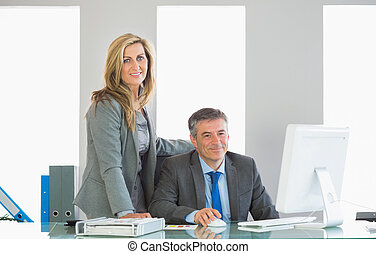 Two joyful businesspeople looking at camera using a computer