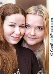 Two joyful Caucasian young women together looking at camera