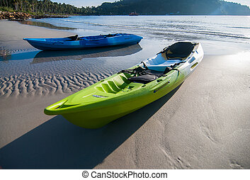 Two kayaks, boats on the beach