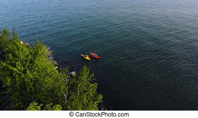 Two kayaks moving on the sea top view. Dog in boat. Sports kayak, canoe in the lake on calm water in autumn day. Tourists canoeing on the Bay. Dog in boat. Aerial drone shot.