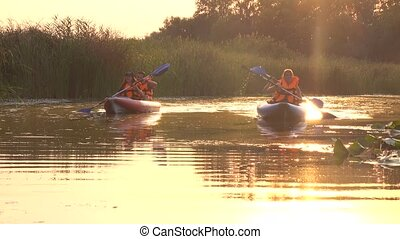 Two kayaks with people rowing oars into the sunset - Two...