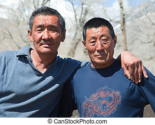 Two Kazakh men pose in the camera on a sunny day
