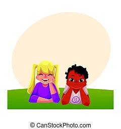 Two kids, black African boy, Caucasian girl, lying on grass