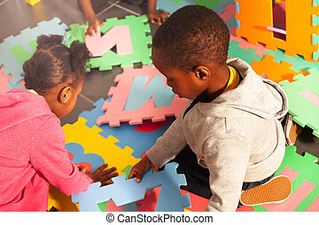 Two kids black boy and girl play with letters