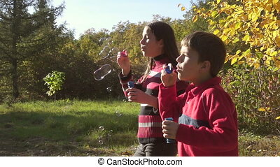 two kids blowing up a soap bubbles, slow motion