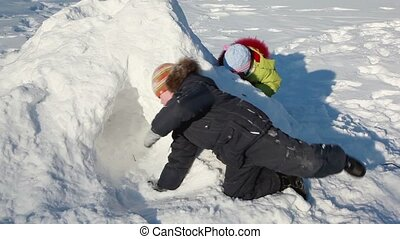 Two kids boy and girl play on snow pile at winter day