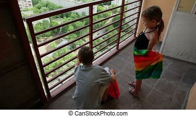 Two kids boy and girl watch on summer cityscape from balcony