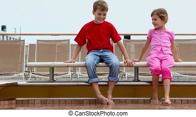 Two kids boy and little girl sit at pool edge near deckchairs