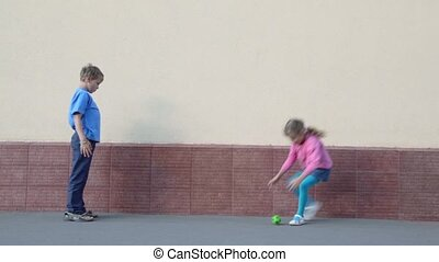 Two kids boy and little girl throws ball to each other near wall