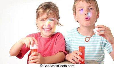 Two kids boy enjoy blows soap bubbles they