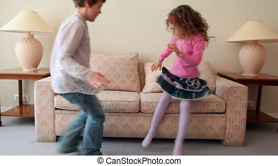 Two kids boy with girl come in room, sit and jump on sofa,...