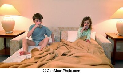 Two kids boy with girl in lay on bed and drink water before sleep