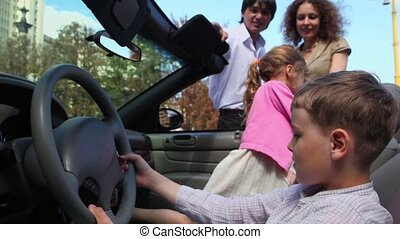 Two kids boy with girl play in cabriolet and parents stand near