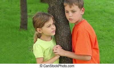 Two kids brother and little sister hold hands near tree and talk