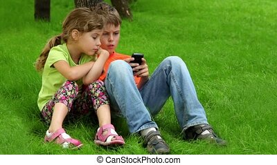 Two kids brother and little sister sit together at grass near tree, boy plays with digital game on cell phone