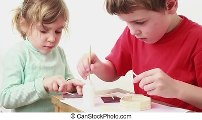 Two kids building match house, girl whet stick and boy glue