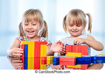 Two kids building with wooden blocks at table.