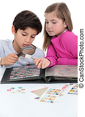 Two kids collecting stamps.