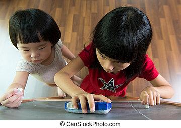 Two kids drawing on blackboard