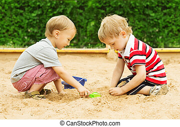 Two kids friends playing with sand outdoor