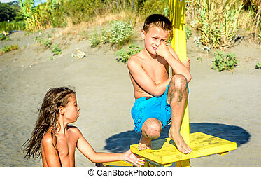 Two kids friends sitting on the beach
