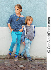 Two kids, girl and little boy, posing outdoors, standing against blue wall, toned image
