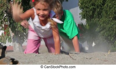 Two kids grabble by sand kicking up dust