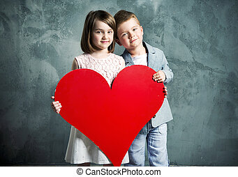 Two kids holding a giant heart