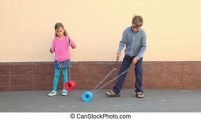 Two kids boy with little girl holds pairs of sticks and plays toy near wall