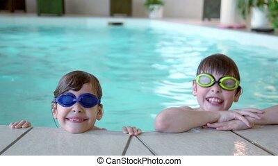 Two kids in swimming glasses stay on pool edge
